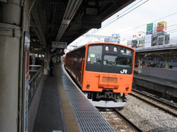 A Chuo Line elevated train pulling into a Japan Railways (JR) station near the center of Tokyo.